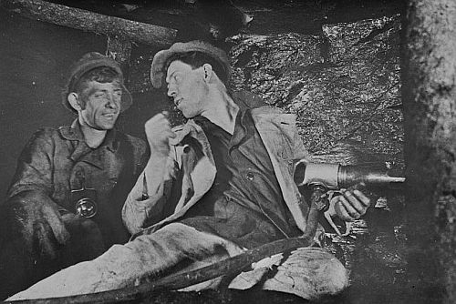Aleksei Stakhanov (centre) speaking to a fellow miner. From the Library of Congress
